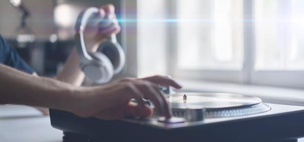 가까운 사람의 손이 파티에서 비닐 디스크를 재생하는 레코드에 바늘을 넣어