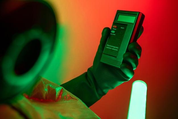 Фотография крупным планом мужчины в защитном костюме от радиации, указывающего на счетчик хегера.