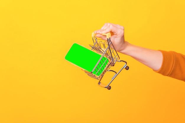 Крупным планом фото женщины, держащей тележку для покупок с телефоном в ней