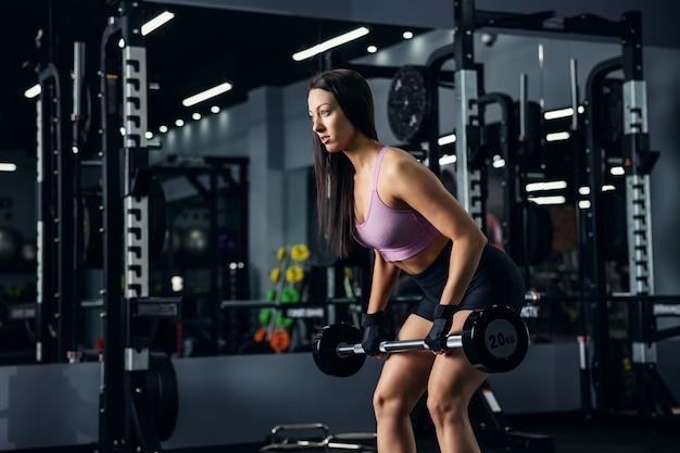 鏡のある暗いジムで強い動きでバーベルを持ち上げる美しい大人のボディービルダーのクローズアップ写真。彼女は成功することを決意している。スポーツ、ボディフォーミング