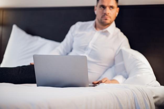 ベッドの中で彼のラップトップを持つ若い男の写真を閉じる