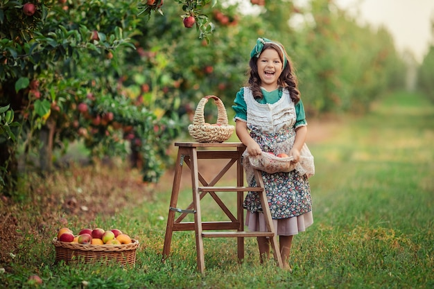 Портрет конца-вверх красивой милой девушки с темными волосами с красным яблоком в ее руках в яблоневом саде на сборе.