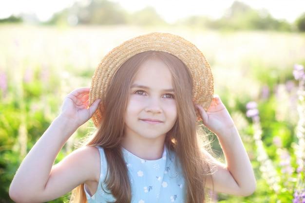 長い髪と麦わら帽子のかわいい女の子のクローズアップの肖像画が開花ルピナスフィールドで再生されます。子供の頃のコンセプトです。コピースペース。子供と自然。国の子供たち。夏休み。ロマンス