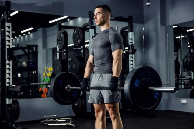 灰色のフィットネスtシャツとショートパンツの男性アスリートのクローズアップの肖像画。彼は屋内スポーツセンターでこれまでで最高のリフティングに心を集中しました。体の力、体力