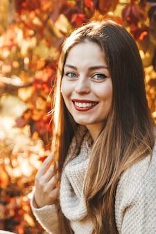 公園の赤と黄色の葉を背景に女性のクローズアップの肖像画。彼女はベージュのセーターを着ており、赤い口紅をつけています。彼女は微笑んでいて、髪は長いです。