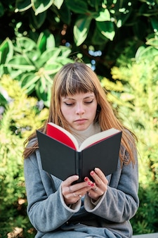 Портрет крупным планом голубоглазой кавказской блондинки молодой женщины, читающей книгу в парке