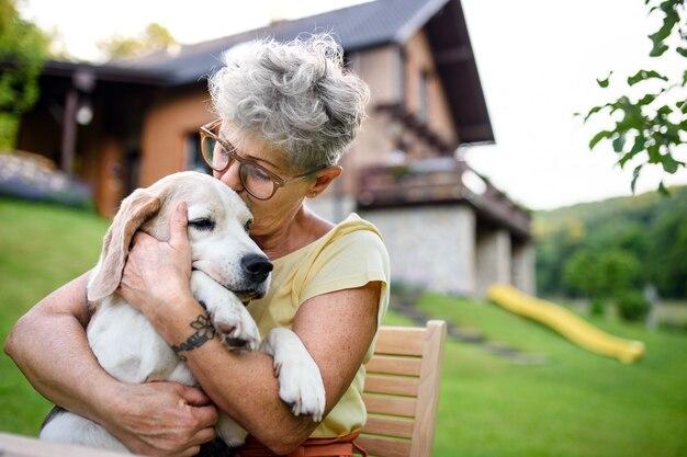 Портрет крупным планом старшей женщины, сидящей на открытом воздухе в саду, концепция дружбы с собакой.