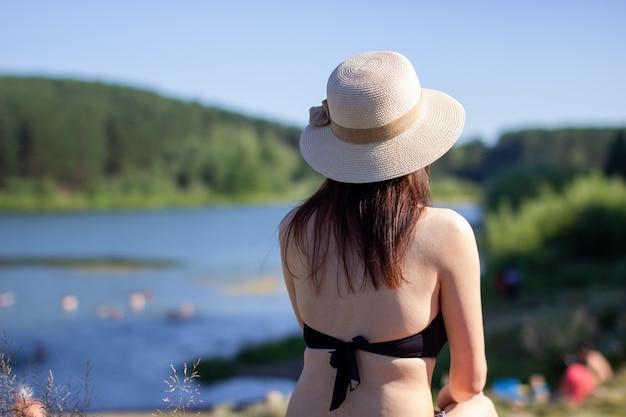 青い湖と空を眺めながら、水着と帽子をかぶった女性の後ろからのクローズアップ。1