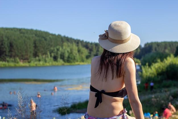 Крупным планом вид сзади женщины, сидящей в купальном костюме и шляпе, смотрящей на голубое озеро и небо.