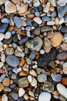 Крупным планом вид гладких полированных разноцветных камней, выброшенных на берег на пляже.