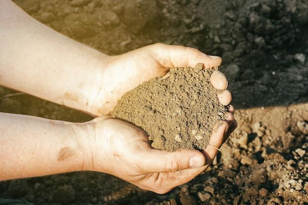男の手の上面図の湿った土壌のクローズアップビュー