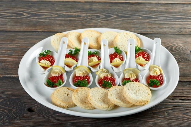 レストランの宴会用に準備されたデリシオスナックのクローズアップ。白パン、赤キャビア、レモンを添えた木製のテーブルの大きなプレート。おやつはとても美味しそうです。