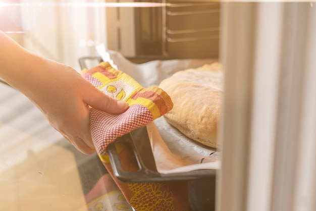 クローズアップの女性の手がオーブンを開き、家で作りたての調理済み食品を取り出します