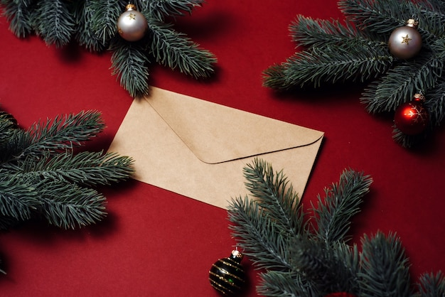Закрытый конверт рядом с елочными ветками и украшениями, шарами.