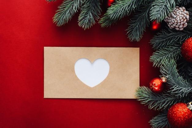Закрытый конверт с вырезанным на нем сердечком рядом с елочными ветками и украшениями, шарами.