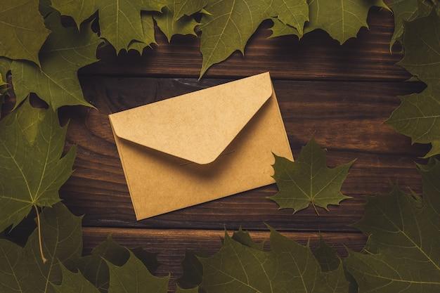Закрытый почтовый конверт в кленовых листьях на деревянном фоне. тонировка. переписка.