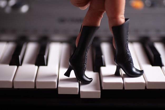 おもちゃの黒い人形のブーツに指が刺さったクローズアップの手がピアノの鍵盤を踏む