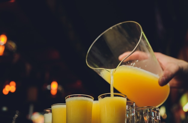 작은 안경에 노란색과 매운 음료 샷을 준비하는 바텐더의 근접 촬영.