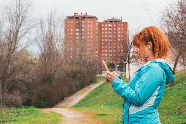 スポーツウェアとヘッドフォンでかわいい赤毛の白人女性のクローズアップは、壁に街と屋外で彼女の電話を見ています