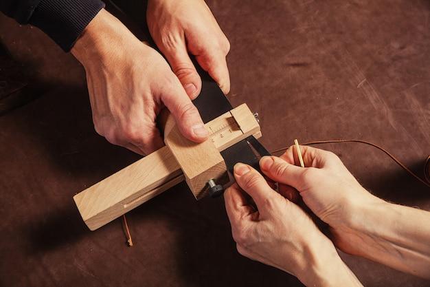 毛皮のクローズアップは革の一部をカットして、特別な機器に黒帯を作成します