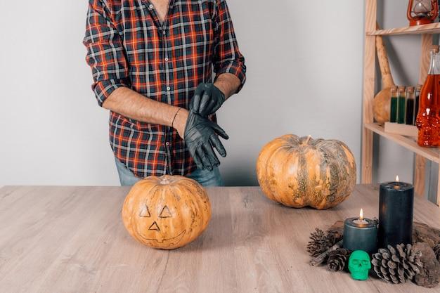 Крупный план человека в латексных перчатках, который готовится вырезать тыкву на хэллоуин