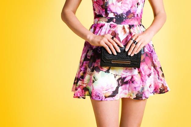 黒い財布を保持しているピンクの花のドレスを着た若いエレガントな女性のクローズアップ