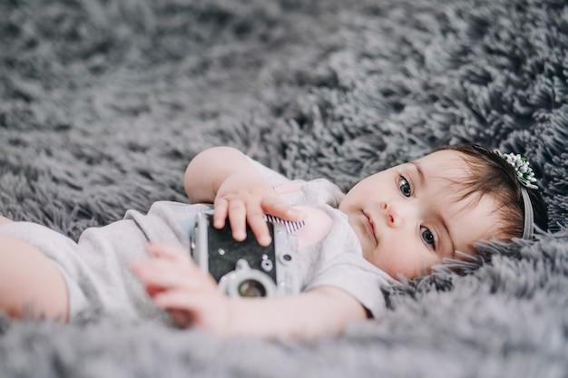빈티지 slr 필름 카메라를 들고 부드러운 회색 시트에 누워 사랑스러운 아기의 근접 촬영