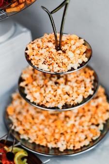 Крупный план соленого попкорна на металлической многоуровневой подставке для свадебного приема