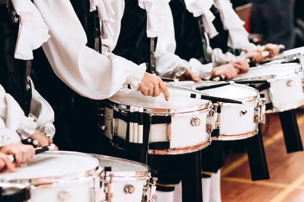 Крупный план рук барабанщика на параде. детский ансамбль в белых рубашках. белый новый малый барабан, белые палочки. концепция военного парада и марша.