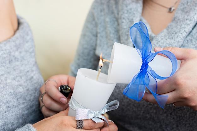 クリスマスのために飾られた2つのキャンドルを照らしている2人の若い女性の手のクローズアップ