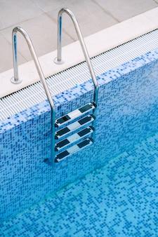 青いモザイクの背景にプールの階段のクローズアップ