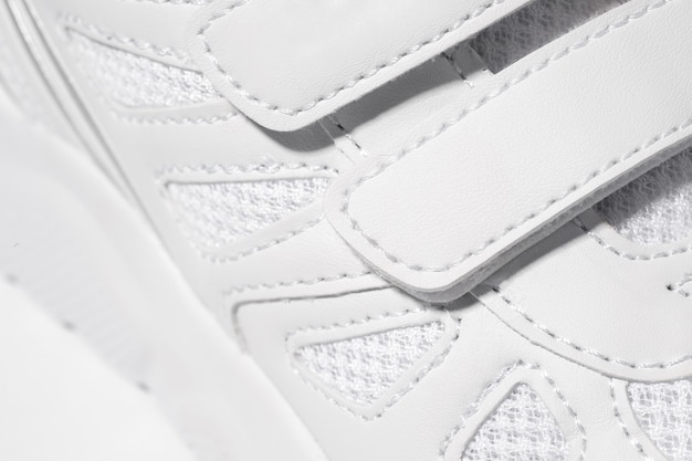 Крупным планом фото застежки-липучки кроссовок. макро фото детских спортивных белых кроссовок, изготовленных ...
