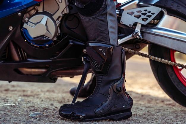 Снимок мужского ботинка крупным планом перед мотоциклом