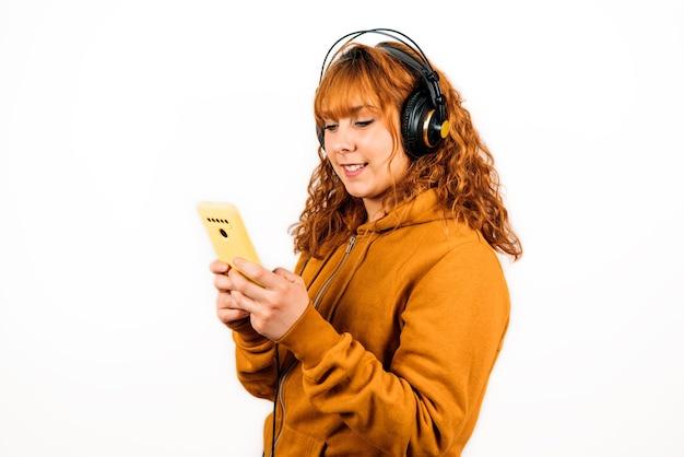 孤立した白い壁に黄色のスウェットシャツで彼女のイヤホンで音楽を聴いている赤毛の女性のクローズアップショット