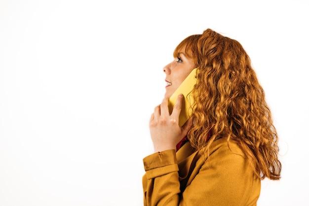 孤立した白い壁に黄色の服を着て電話で話している赤毛の女性のクローズアップショット