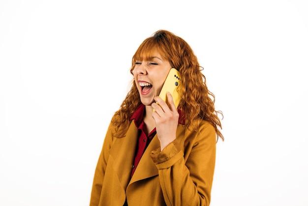 孤立した白い壁に電話で話している赤毛の女性のクローズアップショット