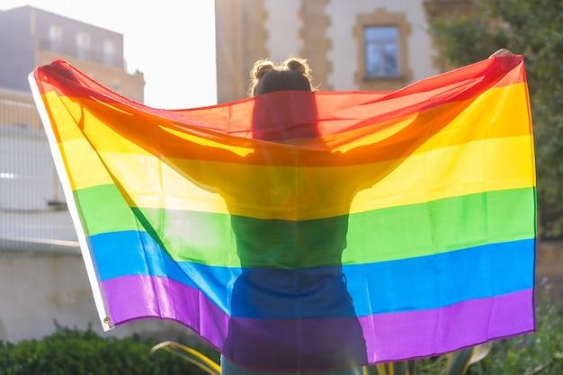 Крупным планом выстрелил молодой кавказской женский силуэт за флагом гордости лгбт на открытом воздухе