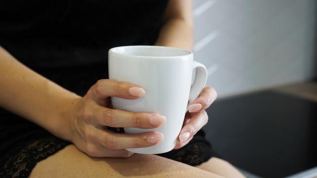 キッチンで彼女の手に白いカップを持っている女性のクローズアップショット
