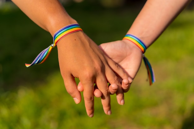 Снимок крупным планом двух молодых кавказских женщин, держащихся за руки с браслетами гордости лгбт на открытом воздухе