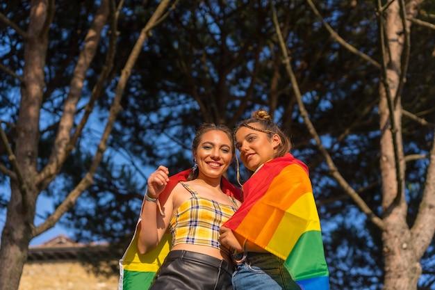 Снимок крупным планом двух молодых кавказских женщин, держащих флаг гордости лгбт на открытом воздухе