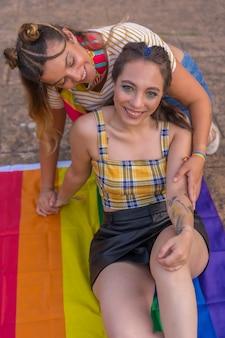 Снимок крупным планом двух молодых кавказских женщин, обнимающихся с флагом гордости лгбт на открытом воздухе
