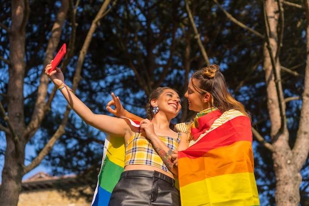 Снимок крупным планом двух молодых кавказских женщин, обнимающихся с флагом гордости лгбт, делающих селфи на открытом воздухе
