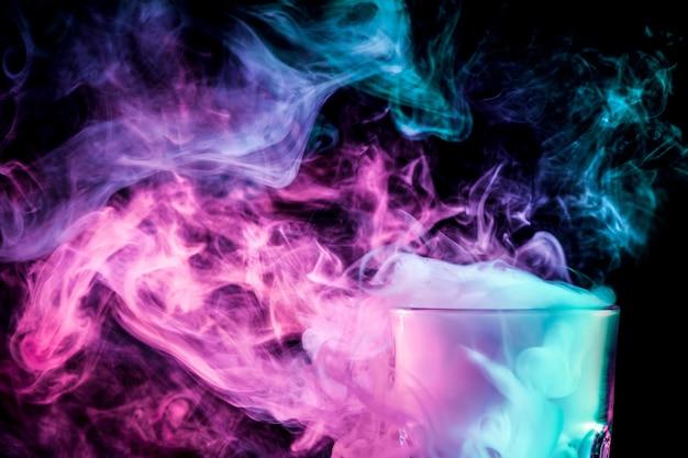 분홍색 vape의 가발로 가득 찬 투명한 유리가 담배를 피우고 서 있다