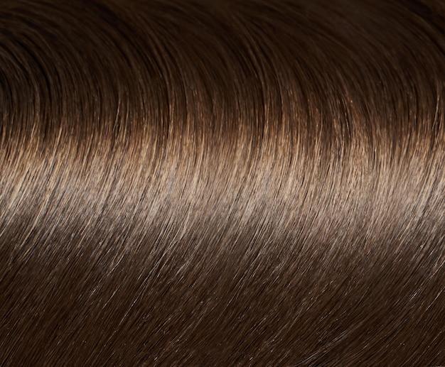 물결 모양의 곡선 스타일로 빛나는 곧은 갈색 머리 다발의 클로즈업 보기