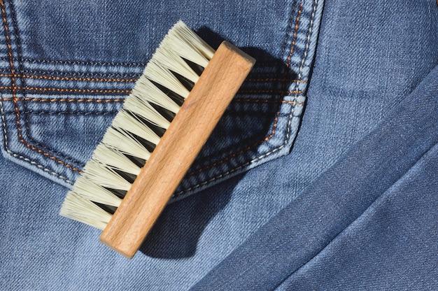 服のブラシは折りたたまれたジーンズの上にあります。