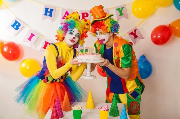 광대 소녀와 휴일에 광대 소년이 생일 케이크를 놓고 싸우고 있습니다.