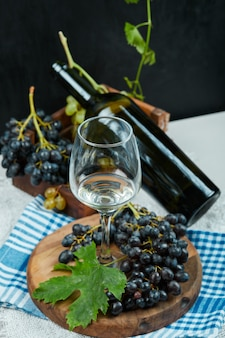 Гроздь винограда с бокалом вина и бутылкой на белом столе с голубой скатертью. фото высокого качества