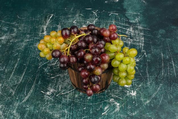Гроздь зеленого и черного винограда на мраморном столе.
