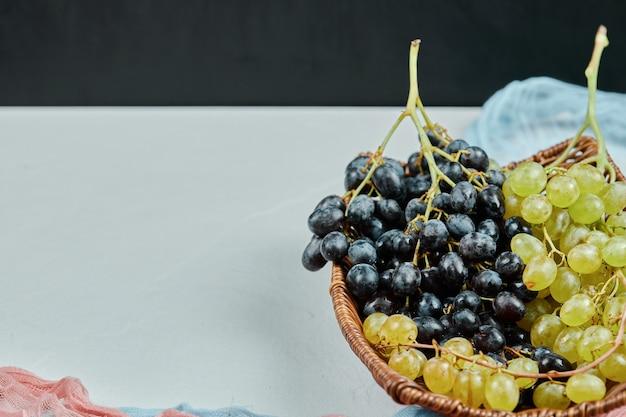 青とピンクのテーブルクロスとバスケットの混合ブドウのクラスター。高品質の写真