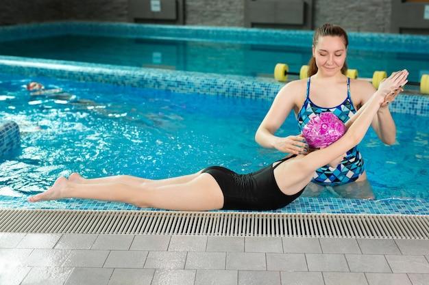 코치는 어린이에게 실내 수영장에서 수영하는 법을 가르칩니다. 측면에서 기술을 보여줍니다.